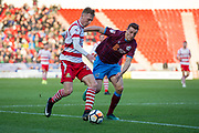 Doncaster Rovers Forward Alfie Beestin (22) (left) holds off Scunthorpe United defender Murray Wallace (5) during the The FA Cup match between Doncaster Rovers and Scunthorpe United at the Keepmoat Stadium, Doncaster, England on 3 December 2017. Photo by Craig Zadoroznyj.