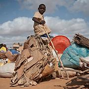kenya, Dadaab, le 19-08-11 - camp de Dagahaley. Il accueille plus de 400 000 personnes, Dabaab est le plus grand camp de réfugiés au monde.  Ce sont pour la plupart des Somaliens (95%) ayant fuit la guerre et la famine, deux fléaux qui sévissent dans leur pays. Les réfugiés installés de façon anarchique dans les périphéries du camp de Dagahaley sont sur le départ.  Devant faire face à la saturation des camps de Dadaab, le UNHCR a décidé de les transférer vers le camp de Ifo 2 ouvert il y a deux jours d'autant qu'ils étaient sur des zones inondables. Un enfant assis sur les afiares de la famille attend le départ