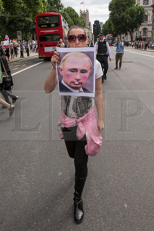 "© Licensed to London News Pictures . 10/08/2013 . London , UK . A protester walks down the middle of the road in Whitehall with an anti Putin banner . Demonstration against homophobic laws being enacted in Russia on Whitehall this afternoon (10th August 2013) . Legislation includes banning gay pride events for100 years , banning the distribution of "" propaganda of non-traditional sexual relations "" to minors , making it illegal for the adoption of Russian children by gay couples or any single person who comes from a country that recognises marriage equality and giving authorities the rights to arrest foreign nationals whom they suspect are LGBT or pro gay with the right to detain them for up to 14 days. Photo credit : Joel Goodman/LNP"