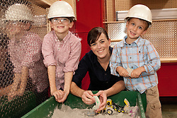 United States, Washington, Bellevue, KidsQuest Children's Museum, mother and sons in hard hats playing at indoor sandbox
