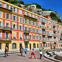 Que Rauba Capéu in Nice, France <br /> Beneath the Colline du Château on Castle Hill is the Que Rauba Capéu, a semi-circular promenade built in 2003 that leads from Nice's Old Town to its harbor.  A colorful, yellow and orange hotel with wrought-iron terraces acts as a backdrop to concrete seats.  These benches serve as an amphitheater for viewing the Côte d'Azur coastline.  Children also enjoy the point to skate beside their parents during family outings.