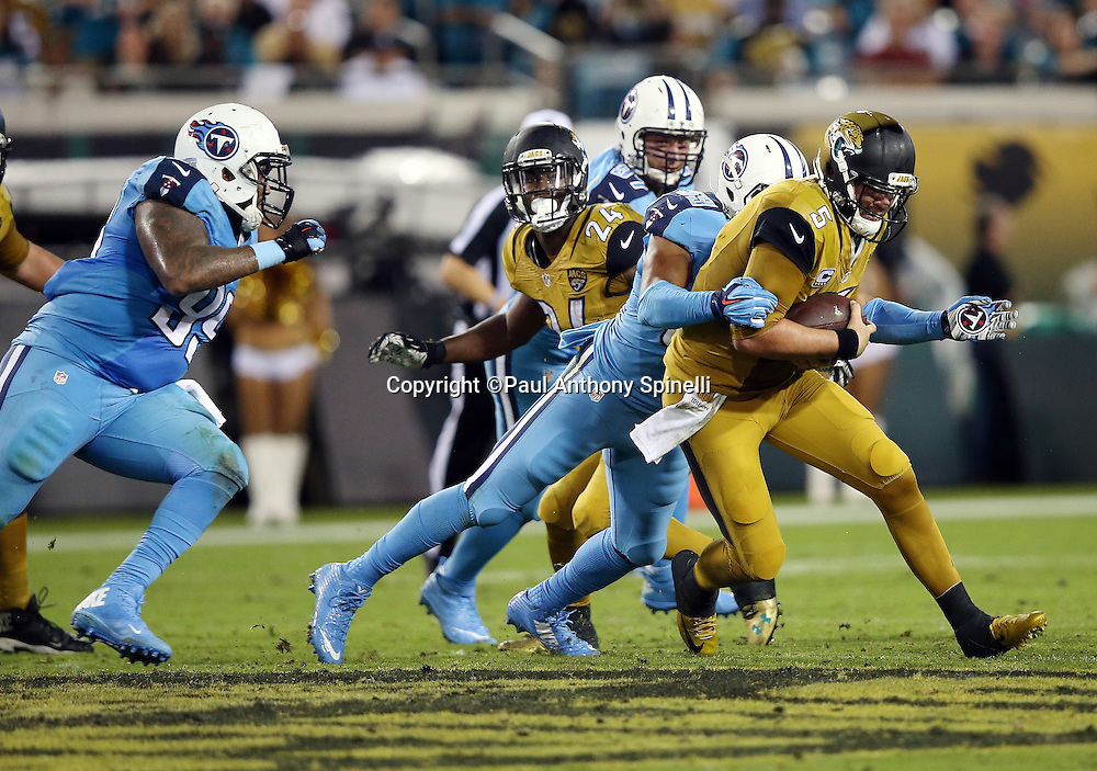 Jacksonville Jaguars quarterback Blake Bortles (5) gets sacked by Tennessee Titans inside linebacker Wesley Woodyard (59) for a loss of 6 yards in the second quarter during the 2015 week 11 regular season NFL football game against the Tennessee Titans on Thursday, Nov. 19, 2015 in Jacksonville, Fla. The Jaguars won the game 19-13. (©Paul Anthony Spinelli)