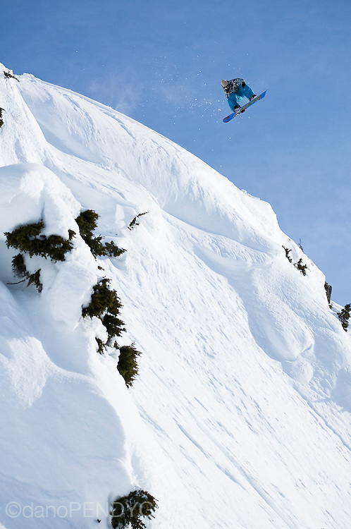Professional snowboarder Mark Landvik sails through the blue skies near Terrace, British Columbia, Canada. Northern Escape Helicopters shuttle skiers and snowboarders into the vast backcountry and have become a winter filming destination for Standard Films.