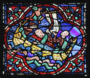 A demon whips up a storm and attempts to sink the boat and destroy the relics of St Stephen. Julienne anxiously watches a man protecting the reliquary with his body. Section of the storm, 1220-25, from the Life of St Stephen and transferral of his relics window in the ambulatory of Chartres Cathedral, Eure-et-Loir, France. This window, unusually dominantly red in colour, tells the story of the life of St Stephen, the first Christian martyr, who died c. 36 AD and whose relics are held at Chartres. It is situated in the chapel dedicated to martyrs. Chartres cathedral was built 1194-1250 and is a fine example of Gothic architecture. Most of its windows date from 1205-40 although a few earlier 12th century examples are also intact. It was declared a UNESCO World Heritage Site in 1979. Picture by Manuel Cohen