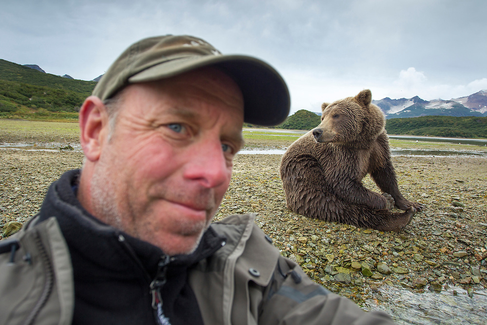 USA, Alaska, Katmai National Park, Self-portrait of photographer Paul Souders sitting near Brown Bear (Ursus arctos) sits nearby along salmon spawning stream