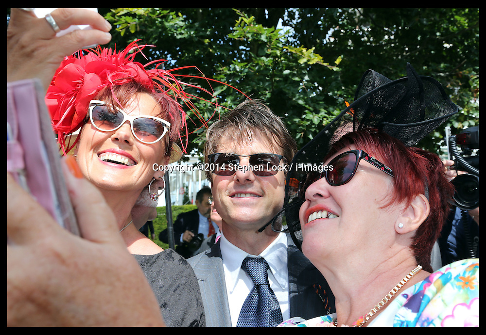 Image licensed to i-Images Picture Agency. 31/07/2014. Goodwood. United Kingdom. Tom Cruise poses for a selfie with racegoers as he arrives  at Ladies Day at Glorious Goodwood.  Picture by Stephen Lock / i-Images