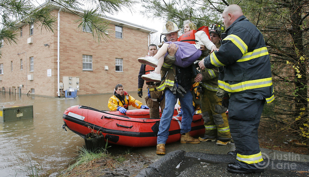 Firefighters evacuate an elderly woman from a flooded housing development (seen at left) in New Milford, New Jersey on Monday 16 April 2007. A large storm delivered records amount of rain to the East Coast of the United States over the weekend and today, causing New Jersey to declare a state of emergency.