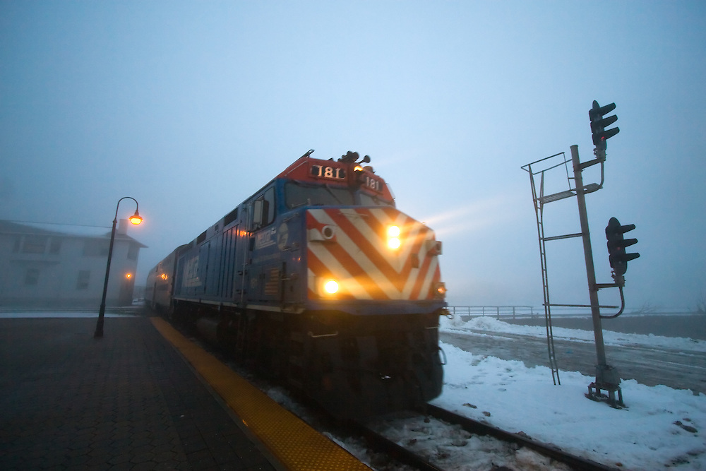 Pulling in to the depot in downtown Joliet, IL, a Metra Rock Island line train is cutting through thick fog during this evening rush hour.