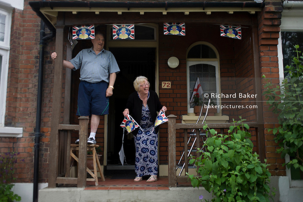 A London couple hang royal bunting the day before Queen Elizabeth's Diamond Jubilee celebrations in the porch of their south London home ahead of a weekend of nationwide celebrations for the monarch's Diamond Jubilee. A few months before the Olympics come to London, a multi-cultural UK is gearing up for a weekend and summer of pomp and patriotic fervour as their monarch celebrates 60 years on the throne and across Britain, flags and Union Jack bunting adorn towns and villages.