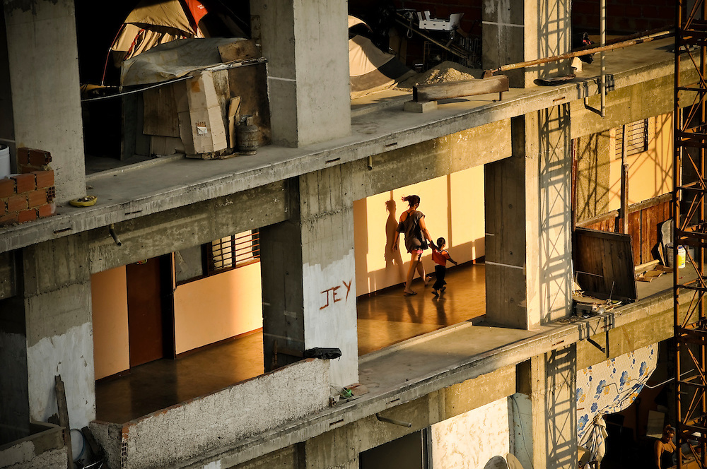 "A woman walks with her young son on an upper floor of the ""Tower of David."" Squatters live in the bottom 28 floors of the 45-story uncompleted skyscraper, located in downtown Caracas, Venezuela. More than 2,500 squatters now occupy the building. Richard Neuwirth, the New York-based author of ""Shadow Cities,"" a book about living in squatter settlements in four continents, said that to his knowledge the Tower of David was the world's highest squatted building."