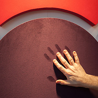 London, UK - 5 February 2014: a man poses his hand on a fabric wrapped acoustic fiberglass absorber by Acoustic GRG iat the Surface Design 2014 show at the Business Design Centre.