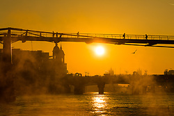 © Licensed to London News Pictures. 10/10/2018. London, UK.  Sunrise on the River Thames as people walk to work over Millennium Bridge during warm and sunny weather this morning.  Photo credit: Vickie Flores/LNP