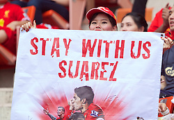 BANGKOK, THAILAND - Sunday, July 28, 2013: A Liverpool supporter with a banner 'Stay with us Suarez' during a preseason friendly match against Thailand XI at the Rajamangala National Stadium. (Pic by David Rawcliffe/Propaganda)