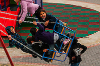 Palestinian kids on a swingset at a playground next to the 16th century ramparts of the Old City, Jerusalem, Israel.