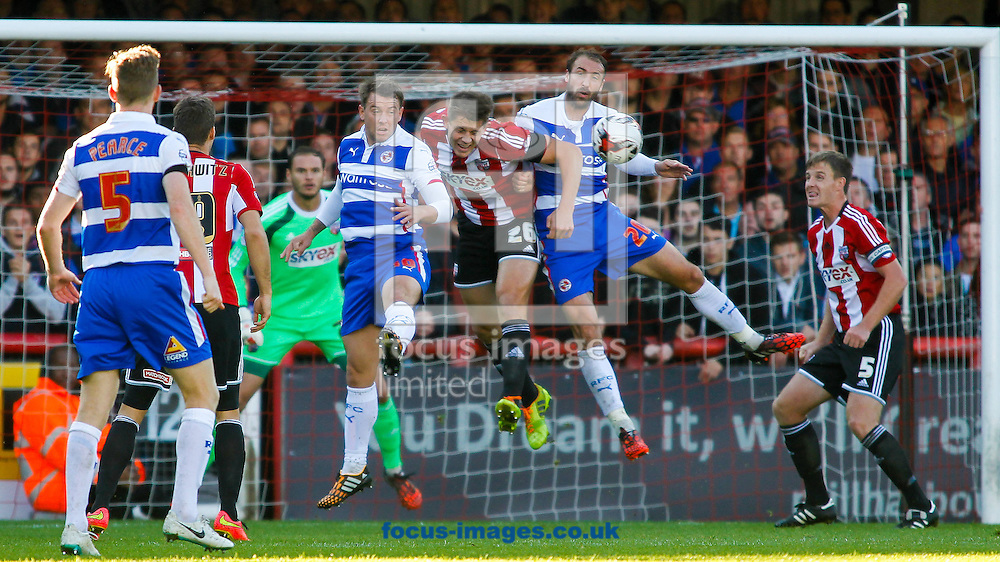 James Tarkowski of Brentford beats Simon Cox and Glenn Murray of Reading to the ball during the Sky Bet Championship match between Brentford and Reading at Griffin Park, London<br /> Picture by Mark D Fuller/Focus Images Ltd +44 7774 216216<br /> 04/10/2014