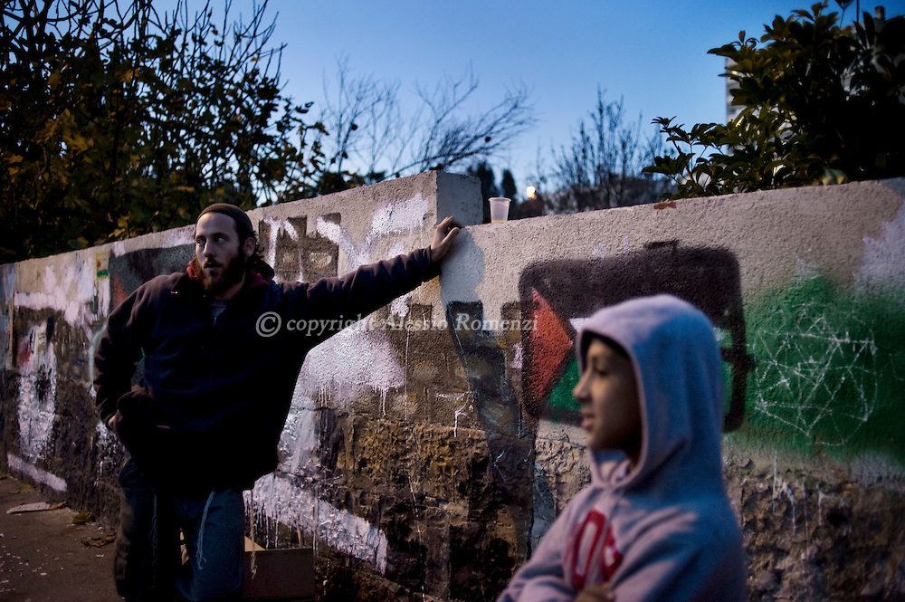 .A Palestinian child and a Israeli settler stand in front of one of the disputed houses occupied by Israeli settlers in the Arab Sheikh Jarrah neighborhood in East Jerusalem, on December 23, 2009..© ALESSIO ROMENZI.