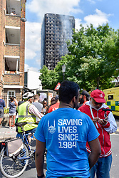 © Licensed to London News Pictures. 14/06/2017. London, UK.   Members of the Islamic Relief charity offer support to local residents as The Grenfell Tower near Latimer Road in west London smoulders after it was engulfed in a huge fire the previous night, resulting in at least twelve fatalities with many more in critical condition. Photo credit : Stephen Chung/LNP