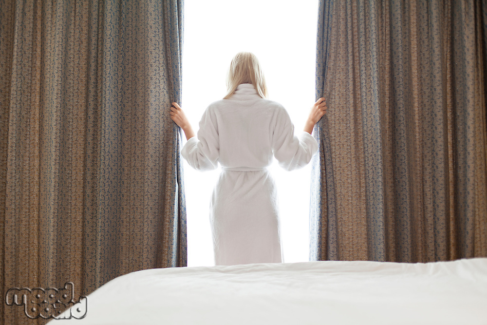 Rear view of young woman in bathrobe opening window curtains at hotel room