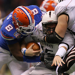 Jan 01, 2010; New Orleans, LA, USA;  Florida Gators defensive end Carlos Dunlap (8) sacks Cincinnati Bearcats quarterback Tony Pike (15) during the first half of the 2010 Sugar Bowl at the Louisiana Superdome.  Mandatory Credit: Derick E. Hingle-US PRESSWIRE.