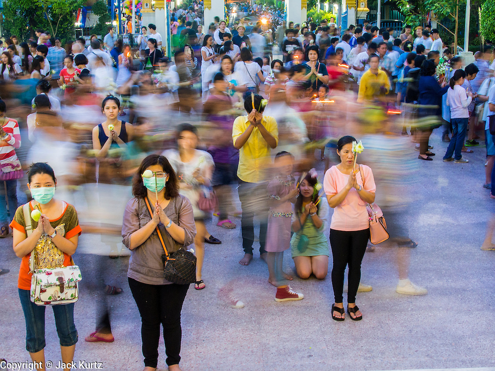 "13 MAY 2013 - BANGKOK, THAILAND: People pray for Vesak on the plaza in front  of Wat That Thong while others walk clockwise around the temple. Vesak, called Wisakha Bucha in Thailand, is one of the most important Buddhist holy days celebrated in Thailand. Sometimes called ""Buddha's Birthday"", it actually marks the birth, enlightenment (nirvana), and death (Parinirvana) of Gautama Buddha in the Theravada or southern tradition. It is also celebrated in Cambodia, Laos, Myanmar, Sri Lanka and other countries where Theravada Buddhism is the dominant form of Buddhism.     PHOTO BY JACK KURTZ"