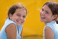 Girls, 10-12, smile at the camera on a sunny day, while sitting in front of a yellow trampoline mattress at the Adventure Zone, Blackcomb Mountain, Whistler, BC Canada.