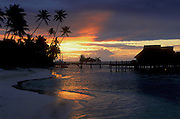 Sunset at Bora Bora Lagoon Resort, Tahiti, with beach, palm trees and overwater bungalows on lagoon..