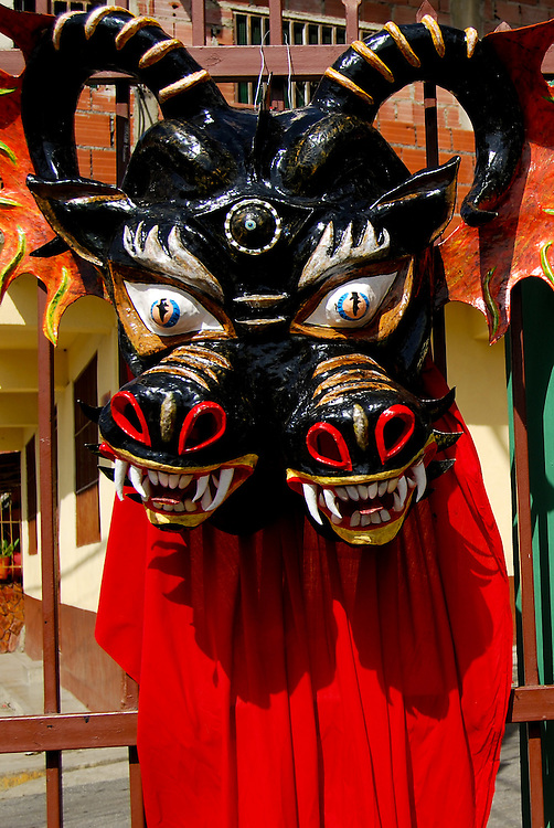DANCING DEVILS OF YARE / LOS DIABLOS DE YARE<br /> Photography by Aaron Sosa<br /> Yare, Mirana State - Venezuela 2009.<br /> (Copyright &copy; Aaron Sosa)<br /> <br /> The Dancing Devils of Yare is a religious festival held in the town of San Francisco de Yare in Miranda State, Venezuela.<br /> <br /> Every Corpus Christi, or 60 days after Easter, men from Yare dress in red robes, capes and masks of grotesque demons and dance in the streets to the rhythm of drumbeats and maracas. They adorn their costumes with scapulars, rosaries, crosses and other religious objects.<br /> <br /> After dancing the devils congregate at the historical San Francisco Catholic church and kneel in silence before being blessed by a priest. The kneeling symbolizes respect and their religious promise to end their evil ways. After being blessed, dancing and music continue as the devils go in a large procession to visit the homes of the deceased throughout their town. The celebration lasts until the end of the afternoon, when church bells are sounded and brotherhood spreads, signifying the triumph of good over evil for one more year.<br /> <br /> The festival's origins date back to the eighteenth century, and being allowed to participate is considered a tremendous honor. The fraternity of men associated with the festival is celebrated as the oldest brotherhood still practicing its traditions, on the entire American continent. Their masks differentiate their place in the fraternity's hierarchy, and it is not uncommon to find men who have danced annually as devils for more than twenty or thirty years.