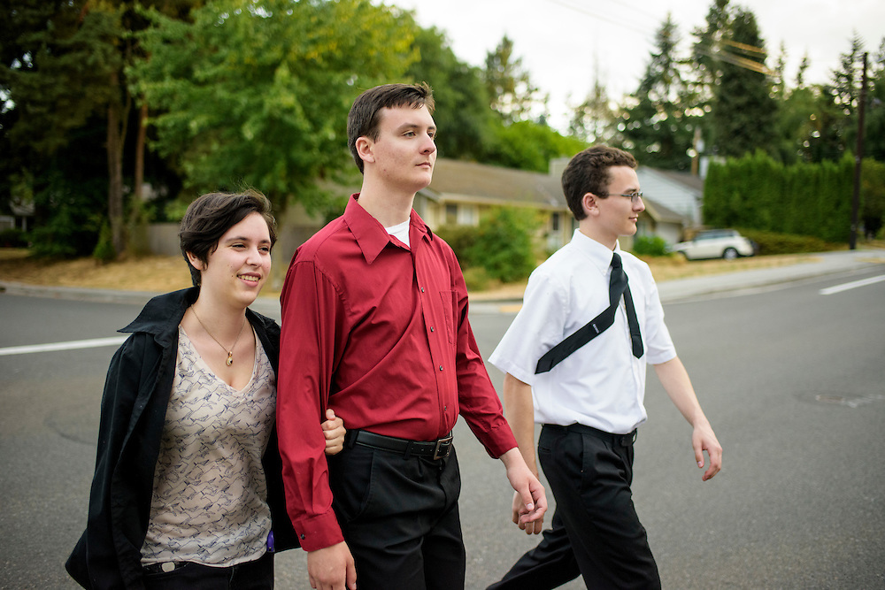 Mountlake Terrace, Washington - July 13, 2015: After dinner, Dictator Dorian Grimes, leader of the Republic of Doria, clutches the arm of her boyfriend King Adam I of &Uuml;berstadt as they walk with Adam's brother Prince Aaron of &Uuml;berstadt. The trio walk from Uberstadt's Creeked Colony to the micronation's Rosewood capitol in the Mountlake Terrace, Washington neighborhood where the two Oberstadt brothers grew up.<br /> <br /> At the end of the summer, Dorian plans to leave Washington to attend college in Los Angeles. King Adam I, who already has his associates degree, is debating wether he should attend college in Northern Washington or go on a Mission representing the Church of Latter Day Saints. <br /> <br /> The Kingdom of &Uuml;berstadt is led by nineteen-year-old King Adam I, (Adam Oberstadt). The Barony of Rosewood -- the micronation's capitol and the Oberstadt family home -- is nestled in the Seattle suburb of Mountlake Terrace, Wash. <br /> &Uuml;berstadt also claims territory of nearby Edmount Island on Lake Ballinger -- called The Barony of Ballinger and &quot;considered the spiritual homeland of the nation.&quot; Both baronies reside within the Duchy of Edmount which &quot;is situated entirely within the boundaries of the city of Mountlake Terrace, Washington,&quot; according to the &Uuml;berstadt website.<br /> &Uuml;berstadt  was founded by King Adam I and his high school friends March 6, 2010, and was governed by judges as a kritarchy. Before taking the crown, Adam was &Uuml;berstadt's chief judge. After graduation, many of the &Uuml;berstadti moved away to college and &Uuml;berstadt's populace shrank. Activities would shift from the high school to Rosewood, and the governing style morphed to a unitary constitutional monarchy. According to the micronation's website &Uuml;berstadt is a sovereign state &quot;guided by the principles of direct democracy, socialist economics, and environmentalism.&quot; <br /> <br /> CREDIT: Matt Roth