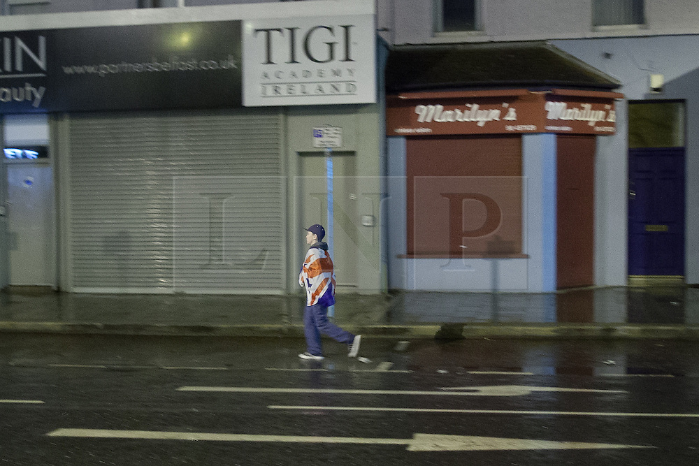"""© Licensed to London News Pictures . 11/01/2013 . Belfast , UK . A boy wrapped in a Union flag walks towards the road block at a Loyalist protesters in Castlereagh , East Belfast , where protesters block major routes in and out of Belfast as part of """" Operation Standstill """" today (11th January 2013) . The protest is one of many that have been held since Belfast City Council voted to stop flying the Union flag above Belfast City Hall . Photo credit : Joel Goodman/LNP."""