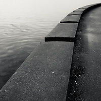 The line and curve of a seawall path along the ocean.