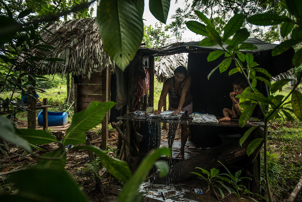 BANGKUKUK TAIK, NICARAGUA - FEBRUARY 9, 2016:   Marbina Albira, 22, washes clothes near her home Bangkukuk Taik, a remote, indigenous village home to the Rama people, and is the point along the Caribbean coast where current construction plans show the Nicaragua canal to start from the Caribbean side of the country. Currently, the village is only accessible by sea. PHOTO: Meridith Kohut for The New York Times