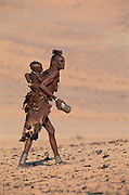 Himba woman carring a baby on her back. Kaokoland, Namibia