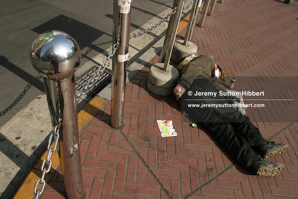 Homeless Japanese man sleeping on the pavement in a busy street in Shinjuku, Tokyo.