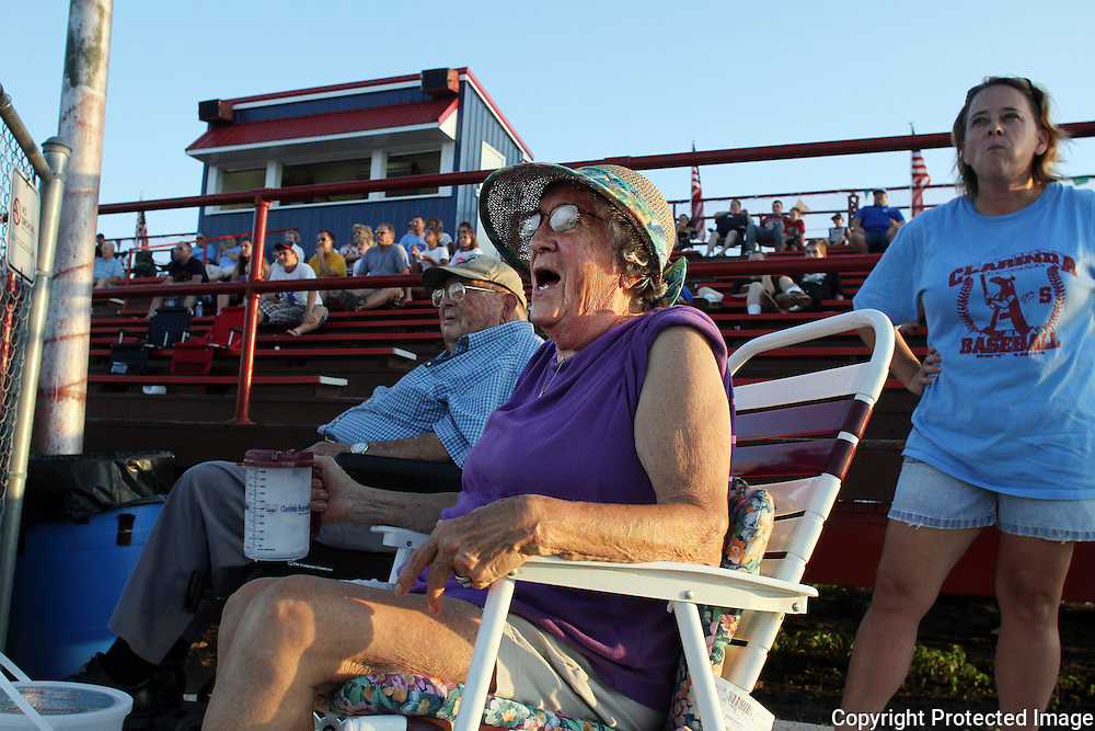 Lois Ellison, 82, cheers for her favorite team, the Clarinda A's, at a home game in July.  Behind Ellison is daughter Kristin Smith.  The Ellison's hosted one of the A's players, John Cade, during the 2010 season.  photo by David Peterson