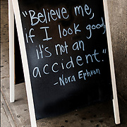 Blackboard quot on sign in front of Hair salon with quote from Nora Ephron. <br />