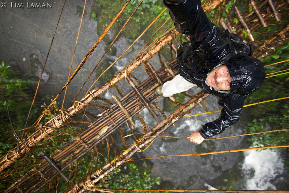 Photographer Tim Laman crossing vine bridge in the rain.