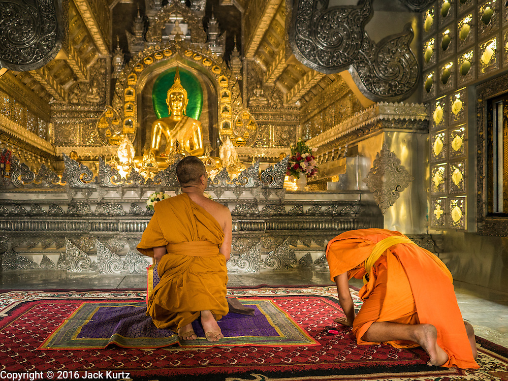 """03 APRIL 2016 - CHIANG MAI, THAILAND: A Buddhist monks pray in the ordination hall of Wat Sri Suphan. Wat Sri Suphan is also known as the """"Silver Temple"""" because of its silver ubosot, or ordination hall. The temple is more than 500 years old but the silver ordination hall was recently remodeled. The ordination hall is covered in silver and the interior is completely done in silver and gold. It's traditionally served as the main temple for the silversmiths of Chiang Mai, whose community is around the temple.     PHOTO BY JACK KURTZ"""