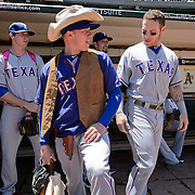 Texas Rangers relief pitcher Robbie Ross, wearing a cowboy outfit, checked out by Texas Rangers first baseman Mitch Moreland before the game at the Oakland Coliseum in Oakland, Calif., June 07, 2012. Pitcher Tanner Scheppers, left, wears a pink backpack on his major league debut.