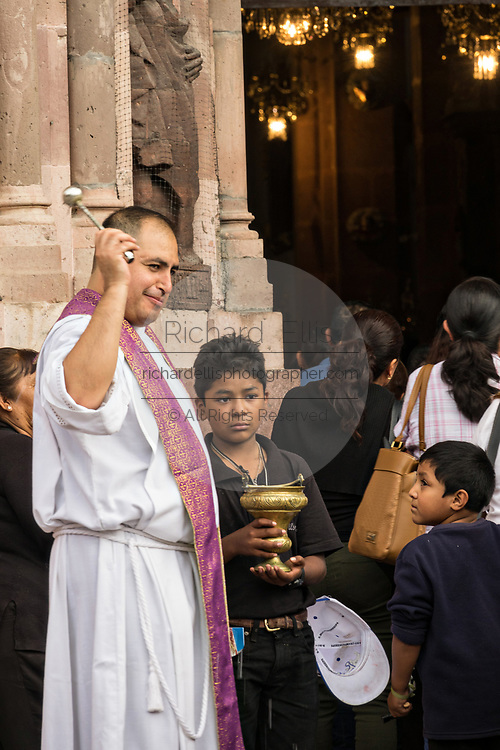 A Catholic priest blesses devotees with holy water as they carry the statue of Saint Michael into the Parroquia de San Miguel Arcangel church during the week long fiesta of the patron saint Saint Michael September 26, 2017 in San Miguel de Allende, Mexico.