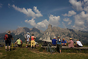 Hikers rest with panoramic views of mountain tops in the Pralongià above San Cassiano-St. Kassian in the Dolomites, south Tyrol, northern Italy. In winter, the Pralongià meadows are the heart of Alta Badia's skiing area.
