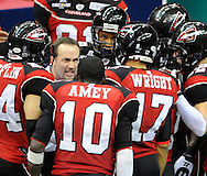 Cleveland head coach Mike Wilpolt, in white, talks to his team during the Gladiators' 61-48 win in their Arena Football League debut on March 3, 2008 at Quicken Loans Arena in  Cleveland against visiting New York Dragons.Ryan Bowers is also in on the play.