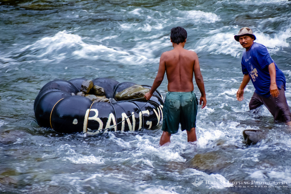Indonesia, Sumatra. Bukit Lawang. These guys are collecting stone from the river in a rafting tube. The stone are later used as building material.