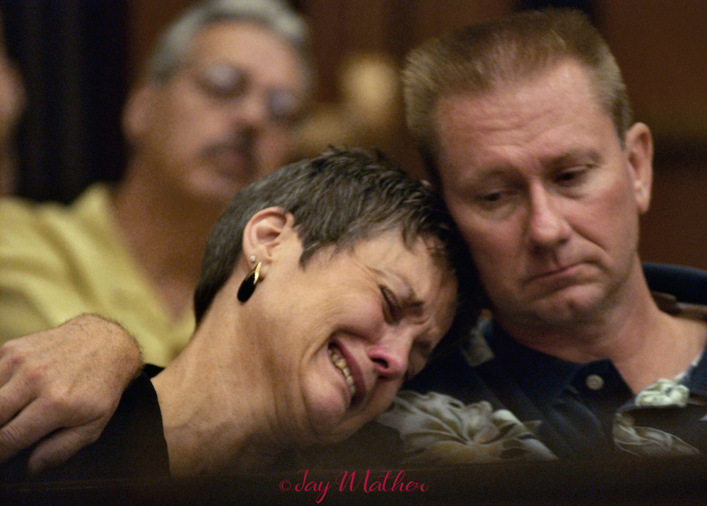 "Chris Wrolstad, left, cries on the shoulder of her husband, Jim Wrolstad, right, after delivering an extremely emotional ""victim impact"" statement during the sentencing of Correll Hicks Jr. for the murder of her daughter, Jessica Smith in a domestic violence incident in September, 2002.  In the background is Rick Smith, the father of Jessica Smith who also gave an emotional statement in court.  Hicks Jr. was sentenced to 26 years to life  in prison for the murder.  The statements the family gave, including ones by Jessica's brother and a cousin, provided a glimpse into grief an extended family experiences long after a domestic violence crime is committed.  The sentencing took place in the courtroom of Judge Michael Garcia in Sacramento Superior Court, Friday, September 10, 2004."