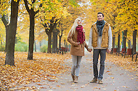 Full length of couple walking while looking up in park during autumn