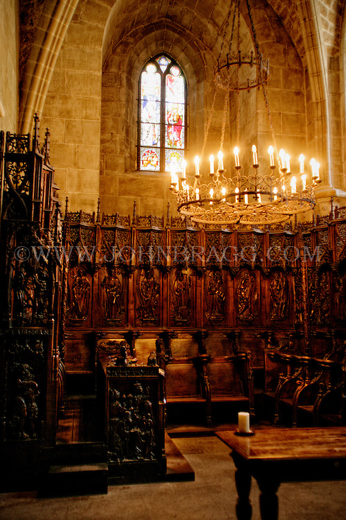 The alter, wood carvings, and wrought iron chandelier taken inside the  Cathedral of Notre Dame of Lausanne, Switzerland