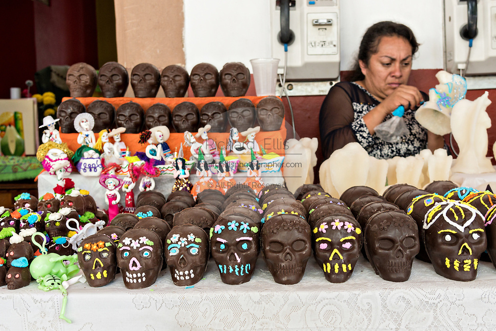 A woman decorates sugar figurines for her stand selling skull candy on display for the Day of the Dead festival October 31, 2017 in Patzcuaro, Michoacan, Mexico.