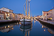 still water reflections at sunset in Cesenatico's harbour in Italy.