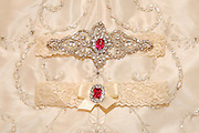Rhinestone and crystal embellished garter set laying on top of the embroidered skirt of the wedding dress
