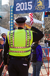 Boston Marathon: BAA 5K road race, Boston police officer salutes during national anthem