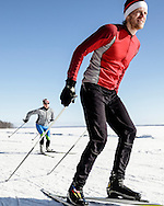 Male and female athletes cross-country skiing on a sunny day.
